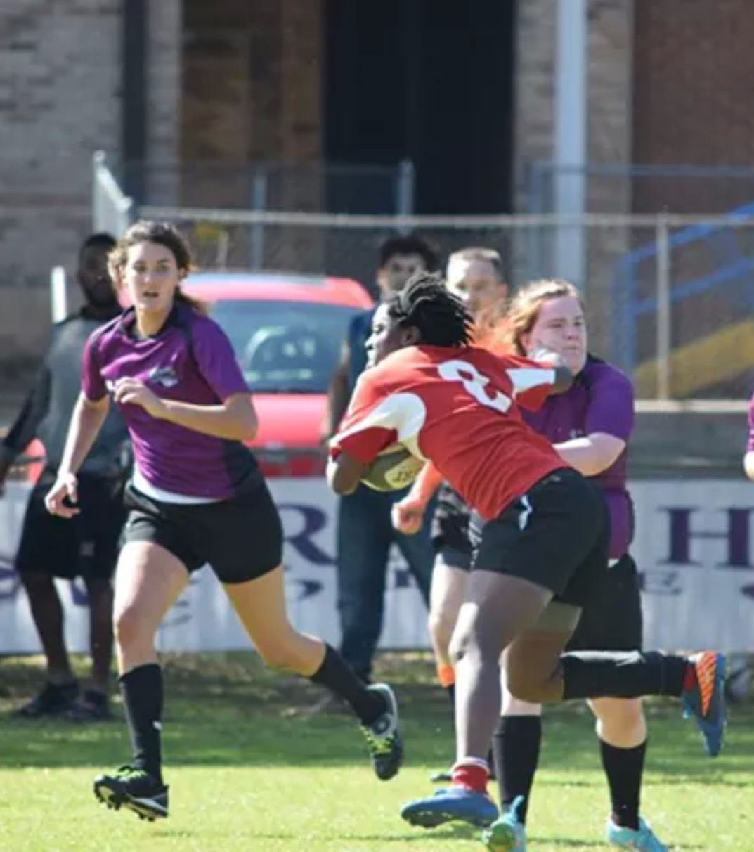Thompson delivers a stiff arm to a defender. Photo Courtesy of Alabama Rugby.